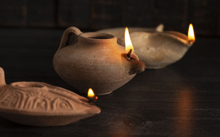 Three Lit Handmade Oil Lamps from the Middle East on a Dark Table