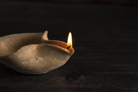 Lit Handmade Oil Lamp from the Middle East on a Dark Table