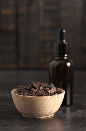 A Bowl of Myrrh on a Dark Wood Table with a Bottle of Essential Oil