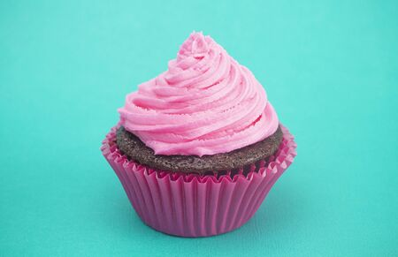 Single Pink Frosted Chocolate Cupcake on a Teal Surface