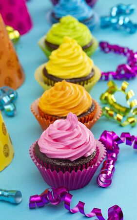 Rainbow Colored Frosted Chocolate Cupcakes on a Teal Background Stok Fotoğraf