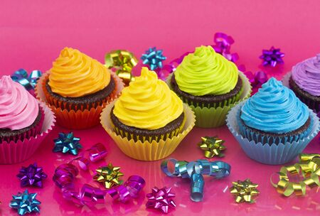 Rainbow Colored Frosted Chocolate Cupcakes on a Pink Background