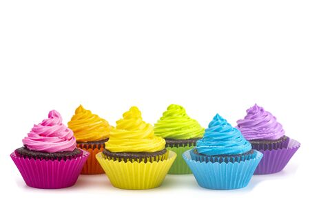 Cupcakes de chocolate esmerilado de color arco iris aislado sobre un fondo blanco. Foto de archivo