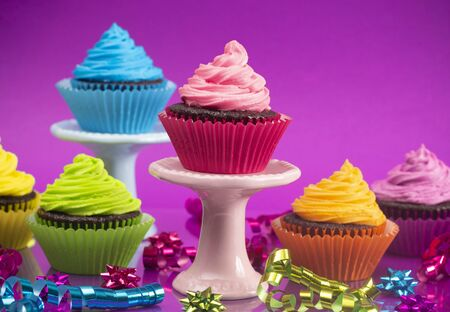 Rainbow Colored Frosted Chocolate Cupcakes with Confetti and Bows Set for a Party