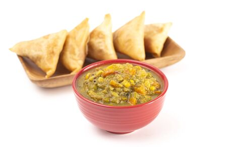 A Spicy Vegetable Curry Isolated on a White Background with Samosas in the Background