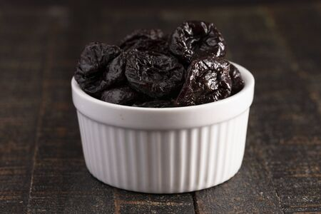 A Bowl of Prunes on a Rustic Wooden Table