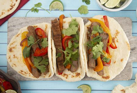 Beef Fajitas with Bell Peppers on a Bright Blue Wood Table Stock Photo
