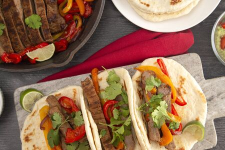 Beef Fajitas with Bell Peppers on a Dark Wooden Table