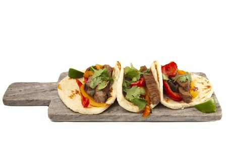Three Fajitas on a Marble Serving Board Isolated on a White Background