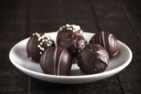 A Moody Image of Chocolate Truffles on a Rustic Wooden Table Banco de Imagens