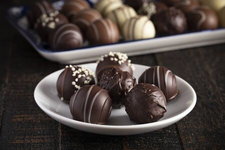 A Moody Image of Chocolate Truffles on a Rustic Wooden Table Stock fotó