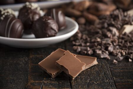 A Moody Image of Various Types of Chocolate on a Rustic Wooden Table Stock fotó