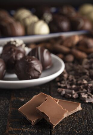 A Moody Image of Various Types of Chocolate on a Rustic Wooden Table 版權商用圖片