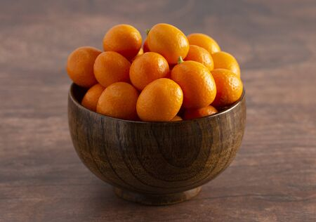 A Bowl of Fresh Kumquats on a Rustic Wooden Table