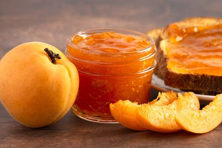 A Jar of Homemade Apricot Jam on a Rustic Wooden Table