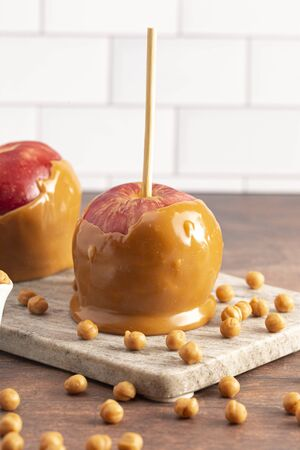Beautiful Caramel Apples on a Rustic Kitchen Cabinet Ready for Fall Stock Photo