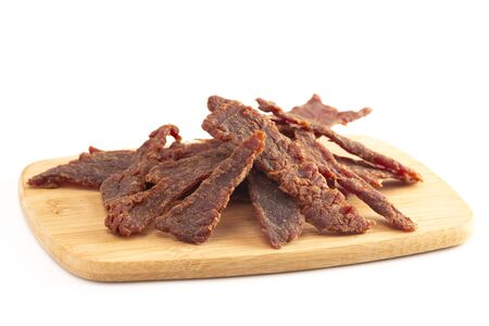 Strips of Beef Jerky on a Cutting Board Isolated on a White Background