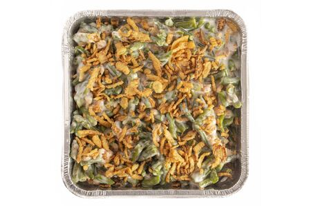 A Pan of Traditional Green Bean Casserole with Fried Onions Isolated on a White Background