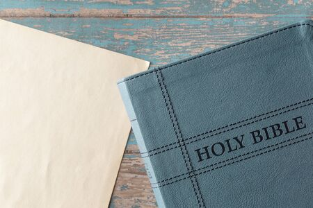 The Holy Bible on a Rustic Wooden Table with a Blank Piece of Antique Paper for Adding Text Stock Photo