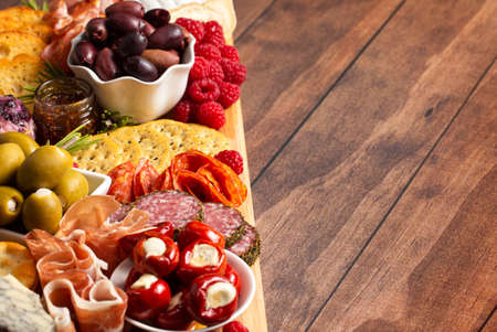 Savoury Charcuterie Board Covered in Meats Olives Peppers Berries and Cheese