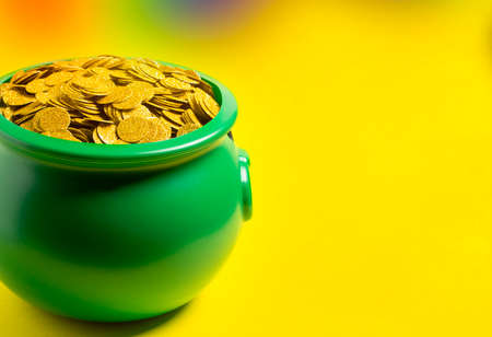 Green Pot Full of Golden Coins on a Bright Yellow Background