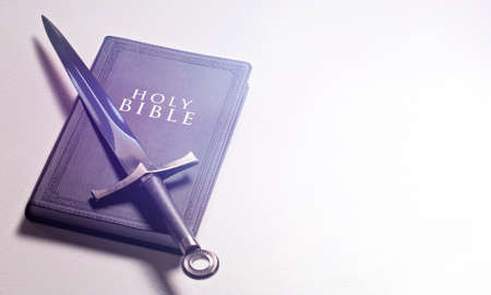 A Bible and Sword on a Bright White Background