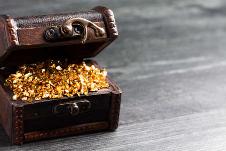Pieces of Gold in a Treasure Chest on a Wooden Table