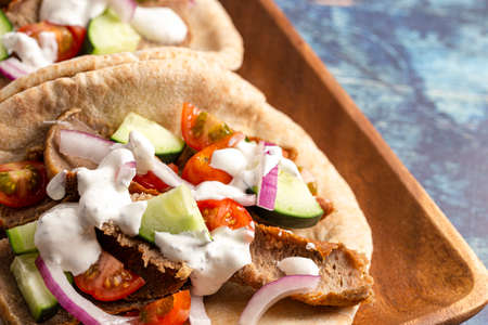 Two Gyros with Vegetables and White Garlic Sauce on a Rustic Wooden Table