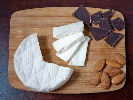 Brie cheese on a wooden cutting board with chocolate and almonds.