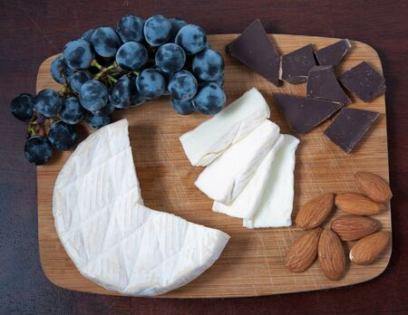 Brie cheese on a wooden cutting board with grapes, chocolate and almonds.