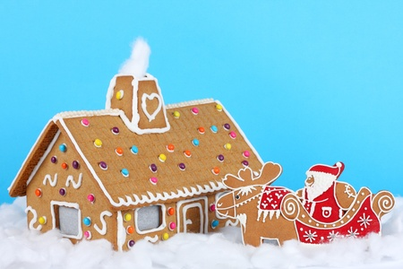 Gingerbread house with Santa Claus on reindeer sled photo