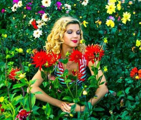 Beautiful girl hugging dahlia flowers on flowers garden photo