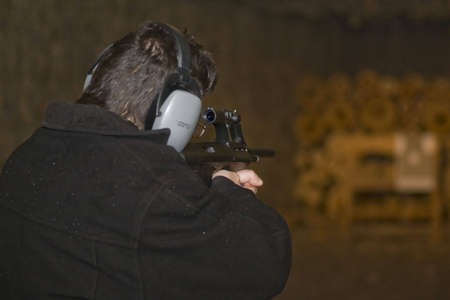 target shooting: Man, aiming an attack rifle to target in shooting gallery, focus on rifle