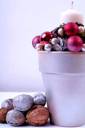 Christmas composition of candle, bright balls and walnuts photo
