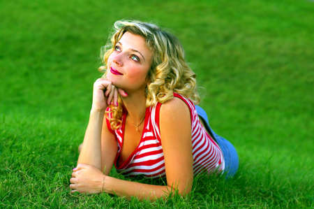 Cute dreaming girl lying on the green grass, staring at the sun Stock Photo - 890589