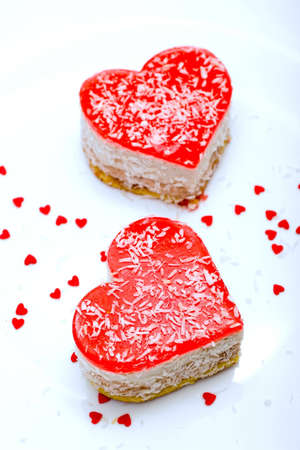 Two jelly heart-shaped cakes on light blue background photo