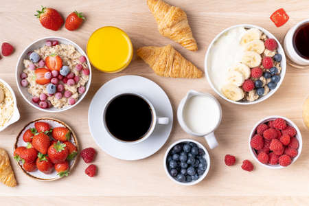 Healthy breakfast set on wooden background. The concept of delicious and healthy food. Mix nuts, honey, berries, orange jus, pancake and milk. Top vi