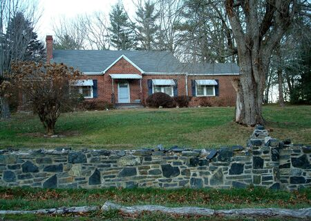 Brick Home On Hill With Rock Wall