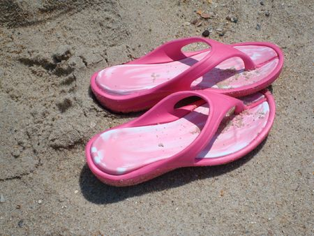 flops: Pink Flop Flops On Sand Stock Photo