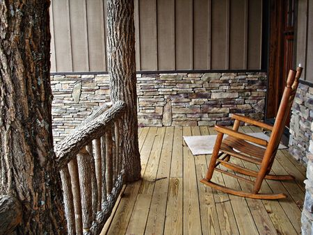 Deck With Rock Work, Log Railing, And Rocking Chair