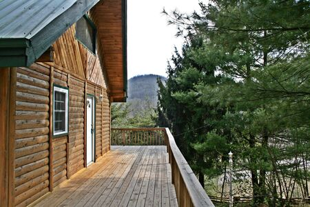 log deck: Mountain Log Home With Large Deck Stock Photo