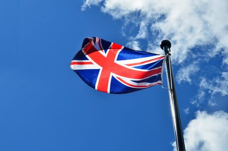 An image of an old British flag flying against a bright blue sky.