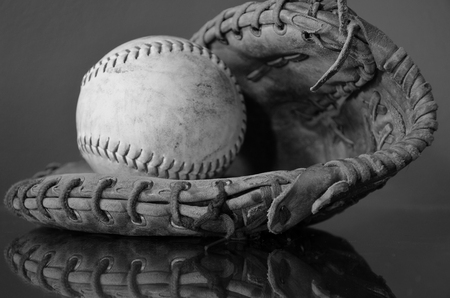 baseball glove: A black and white image of an old leather baseball and baseball glove.