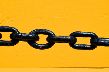 link up: An abstract image of a black chain against bright yellow painted wood. Stock Photo