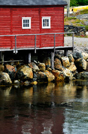 wooden dock: An image of a red building with an old wooden dock. Stock Photo