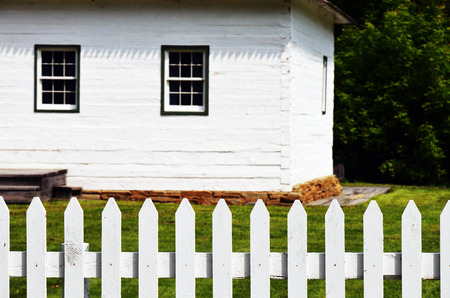 picket: A partial view of an old white house with white picket fence.