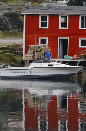 lobster boat: An image of a boat docked beside a bright red building and a dock with lobster traps.
