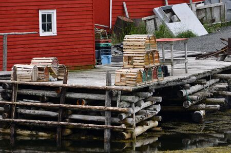 wooden dock: An image of lobster traps on an old wooden dock beside a bright red building.