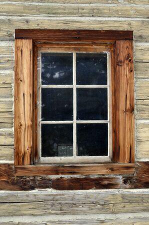 An image of a window on an old log building