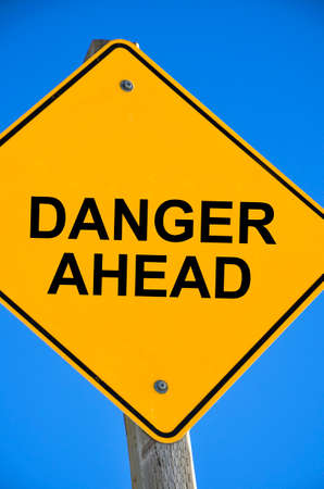 danger ahead: An image of a bright yellow road sign which reads Danger Ahead.